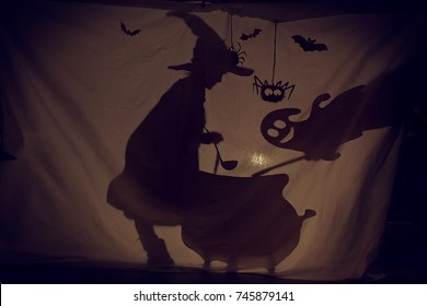Fabulous shadow the little witch at the cauldron brews a potion with a Ghost.The theatre of shadows. . Childhood. A magical story.Halloween.