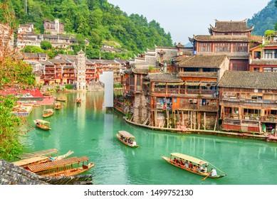 中国鳳凰古都町(鳳凰郡)の、ツオジアン川(トウジアン川)に面した伝統的な木製の観光船の素晴らしい眺め。和明の塔は背景に見える。