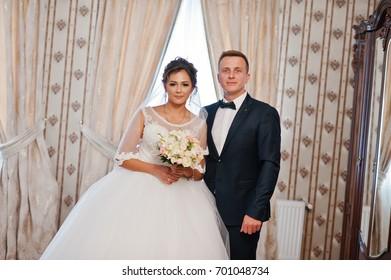 Fabulous wedding couple posing in the bride's room.