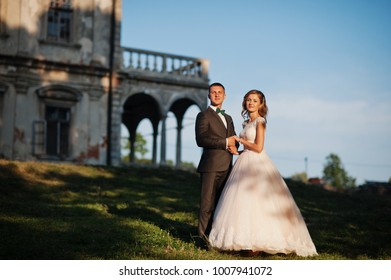 Fabulous wedding couple posing in front of an old medieval castle in the countryside on a sunny day.