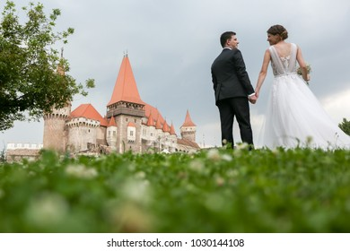 Fabulous wedding couple posing in front of an old medieval castle in the countryside