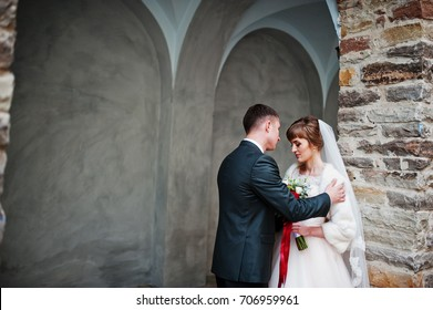 Fabulous wedding couple walking and posing next to the old building.