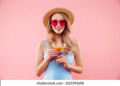 Fabulous woman in sunglasses wearing one-piece swimsuit and straw hat smiling while holding glass of orange juice isolated over pink background