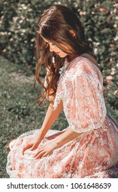 fabulous, young girl with beautiful hair in a vintage pink dress in the garden