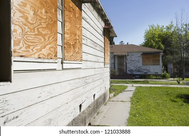 Facade of an abandoned house with boarded up windows