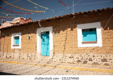Facade of an adobe house with mint blue doors between the streets of a magical town located in the state of Mexico