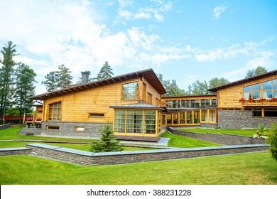 Facade of a beautiful wooden house with green garden