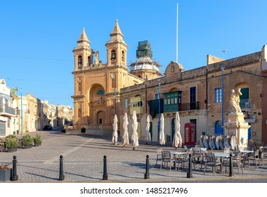 Facade and belfries of the old church of St. Peter on a sunny morning. Marsaxlokk. Malta.