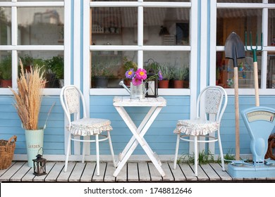 Facade blue Cozy home with a beautiful garden in summer. Beautiful farmhouse with wicker baskets and green plants on terrace. White table and chair on veranda of house. Yard with gardening tools.