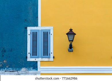 Facade in blue and yellow with windows and street light