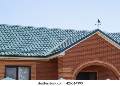 Facade of a brick building with a green roof made of metal. Roof metal sheets. Modern types of roofing materials.