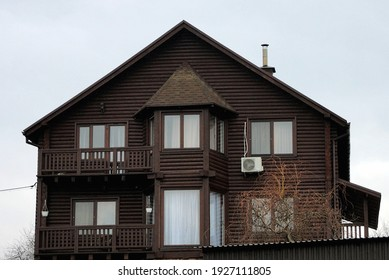 facade of a brown private wooden house made of logs with windows and bucks against a gray sky
