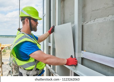 facade builder installing tile on wall