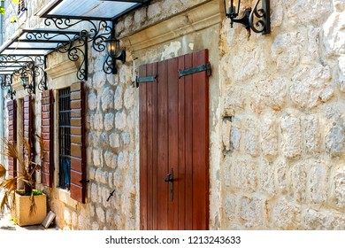 Facade of the building of the authentic old town of Perast, Montenegro. We see an old house with windows and wooden shutters.
