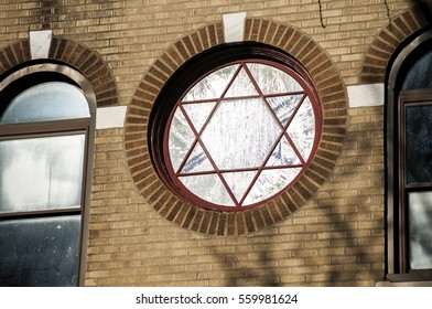 Facade of building with circular painted glass window with Jewish pentagram