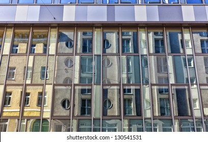 Facade of a building in a contemporary architecture style with the reflection of an old building opposite