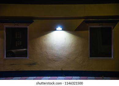 Facade of a building with two window lit by a street lamp at night