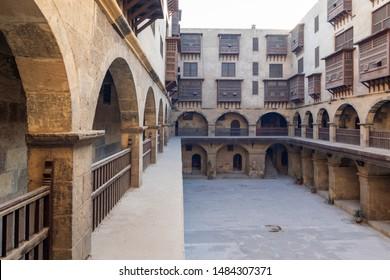 Facade of Caravanserai of Bazaraa, with vaulted arcades, windows, and arab oriel windows - mashrabiya - suited in Tombakshia street, Al Gamalia district, Medieval Cairo, Egypt
