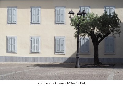 Facade of a central european town palace from the early twentieth century, with a lamppost, an olive tree. and a  porphyry street. Background for copy space.