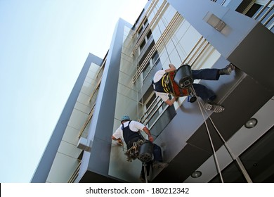 Facade Cleaning. Glass Cleaning Services.  Workers washing the windows facade of a modern office building.