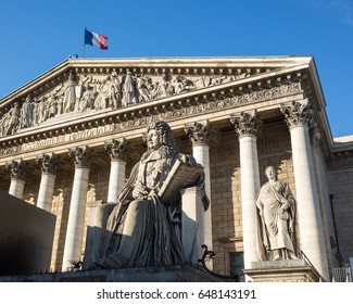 Facade with colonnade of the Palais Bourbon in Paris, seat of the french National Assembly, with the statue of Francois d'Aguesseau and the french flag flying on the roof against blue sky.