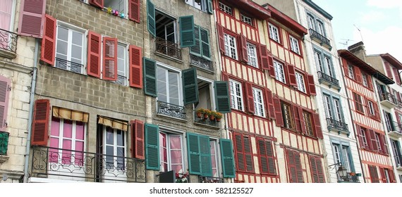 Facade of colorful houses with green and red wood windows. Small balconies in the city of Bayonne, South of France