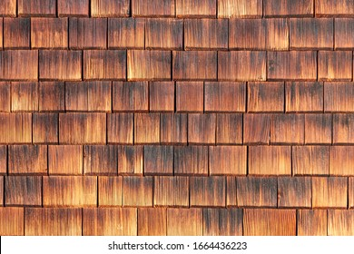 Facade covered with wooden weathered shingles.