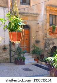facade detail of an old building in the historic center of Agrigento with doors and windows and flower pots decoration. Agrigento Sicily. Italy