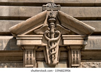 Facade details, symbol of medicine with staff and two snakes. The symbol of the god Hermes or Esculap in little Paris - Bucharest, Romania.