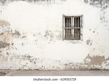 Facade of a dilapidated blank wall with a barred window.