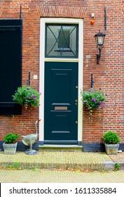 Facade of Dutch brick wall house, front door, shutters, lantern, duck statue and flower pots in popular neighborhood street, Netherlands