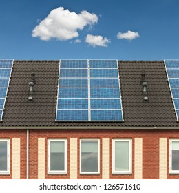 Facade of a Dutch row of new houses with solar panels