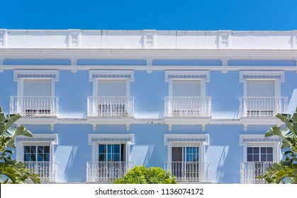 the facade of an elegant blue and white building against a blue sky. There are shutters on the balconies with metal railings.