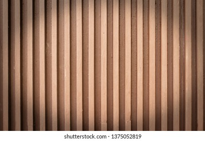 facade element with alternating vertical wooden or concrete slats and brown and pink slats