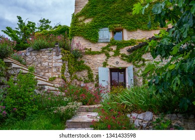 Facade with flowers of old French house. Picturesque typical french rural house decorated with green plants and flowers. Garden with colorful plants in summer season.