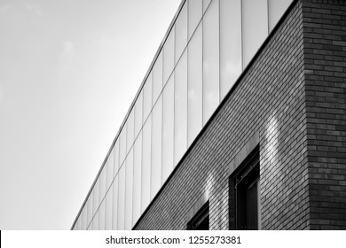 Facade fragment of a modern office building. Exterior of glass wall with abstract texture. Black and white.