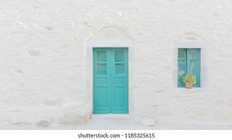 The facade of a genuine Greek house on the Cyclades. Turquoise doors and window against a white wall. Minimal