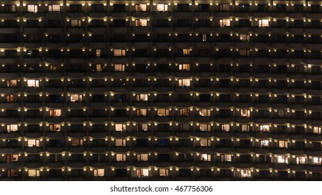 Facade of highrise apartment block with balconies. Electric lights in some windows. Housing in Bangkok, Thailand