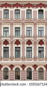 The facade of a historic building. Burgundy bas-reliefs on the Windows