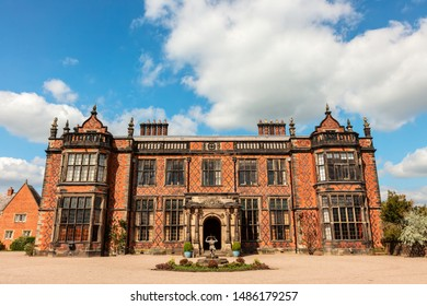 Facade of an historic English mansion in red brick.