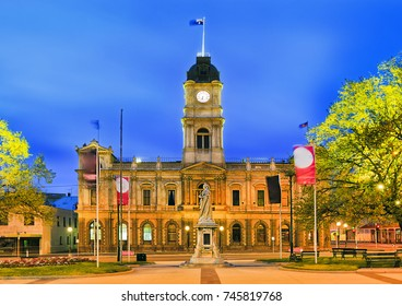 Facade of historic Town hall building in regional centre in Victoria state - Ballarat. Brightly illuminated at sunrise with Queen Victoria statue in foreground.
