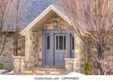 Facade of a home with a beautiful stone wall and gray front door