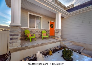 Facade of home with bright orange front door decorated with a festive wreath
