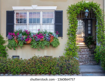 Facade of a home in downtown Charleston, South Carolina with iconic window box filled with flowers in bloom and ivy covered doorway arch.