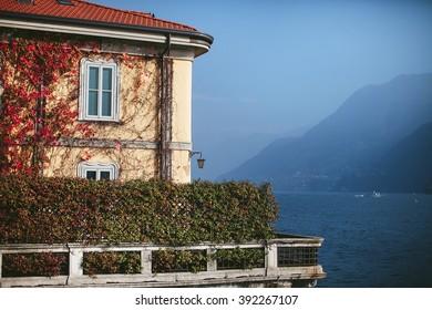 facade of the house with bushes on the shore of a mountain lake como