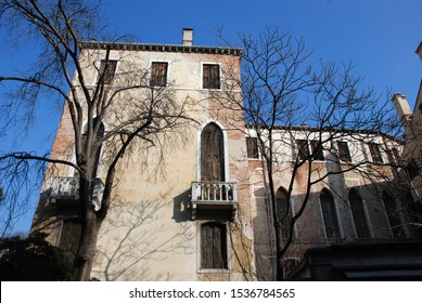Facade of a house in Venice Italy, wooden doors and windows with typical arcades balcony with baluster on a sunny winter day