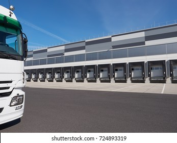 Facade of an industrial building and warehouse with truck waiting for cargo
