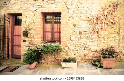 Facade of the Italian house, decorated with fresh flowers in pots and dry corn cobs. Vintage style.