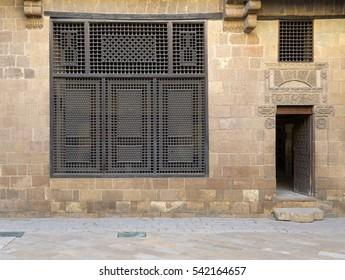 Facade (Mashrabiya window and open wooden door on stone wall) of a historic eighteenths century house in Medieval Cairo, Egypt