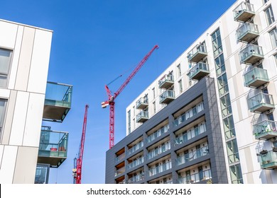 Facade of a modern flat with building cranes in the background